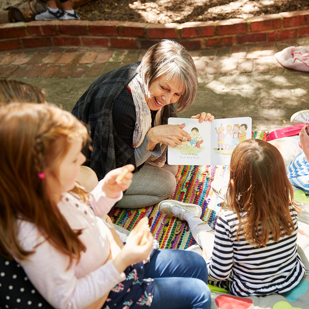 Woman reading with children in the courtyard