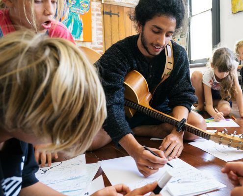 Young man with guitar and children composing music